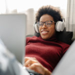 woman listening to and watching recordings from Virginia's premier orchestras