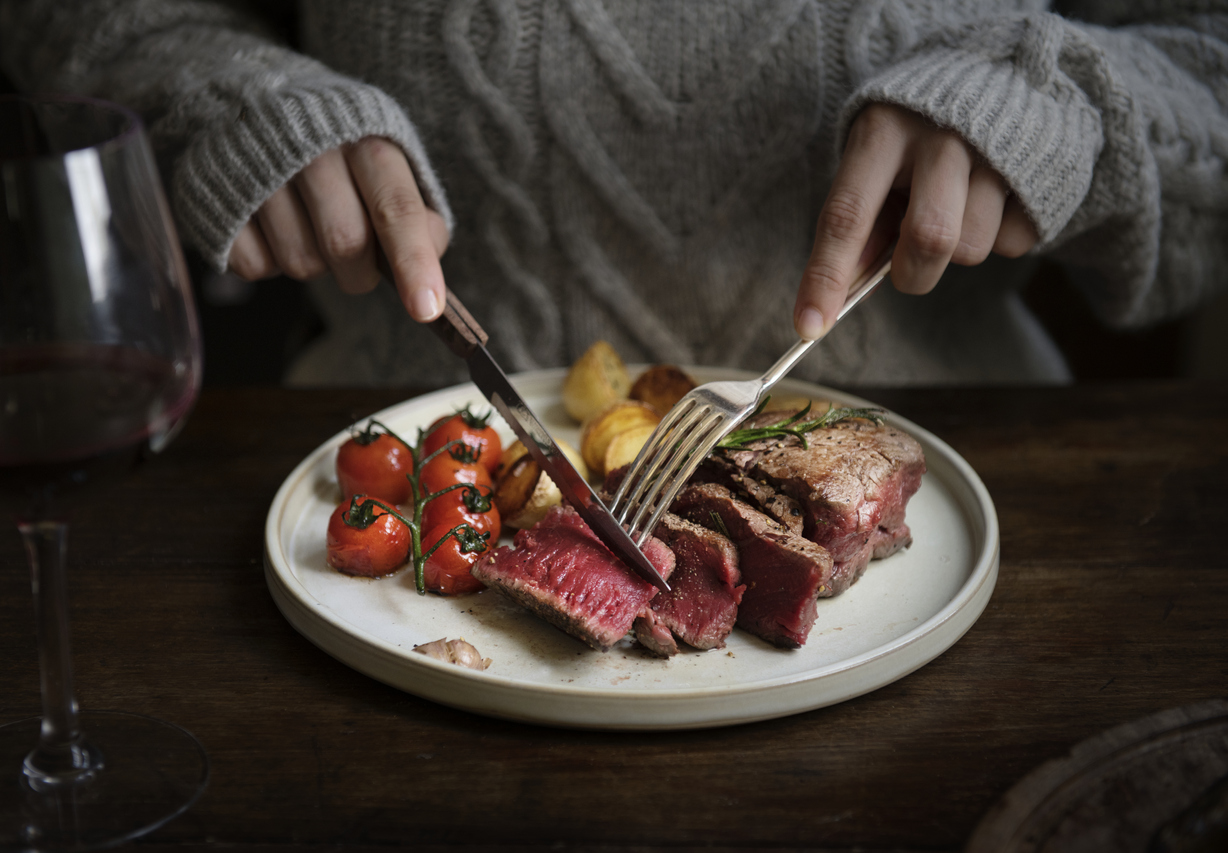 woman cutting into a steak dinner
