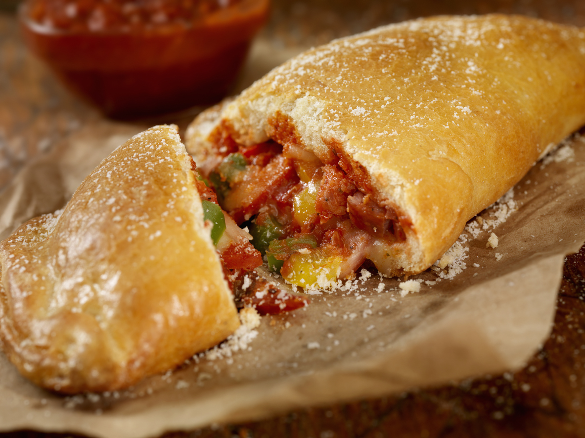 Italian calzone with pepperoni, sausage, peppers, fresh parmesan and marinara sauce