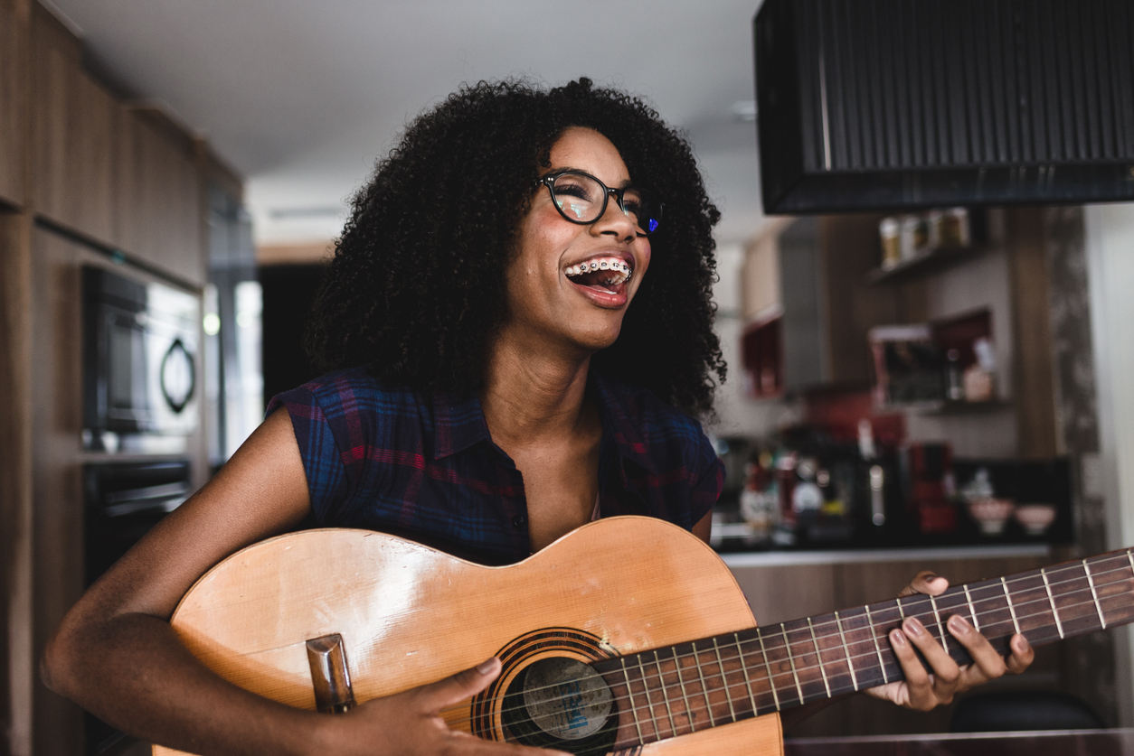 woman learning how to play a guitar at home