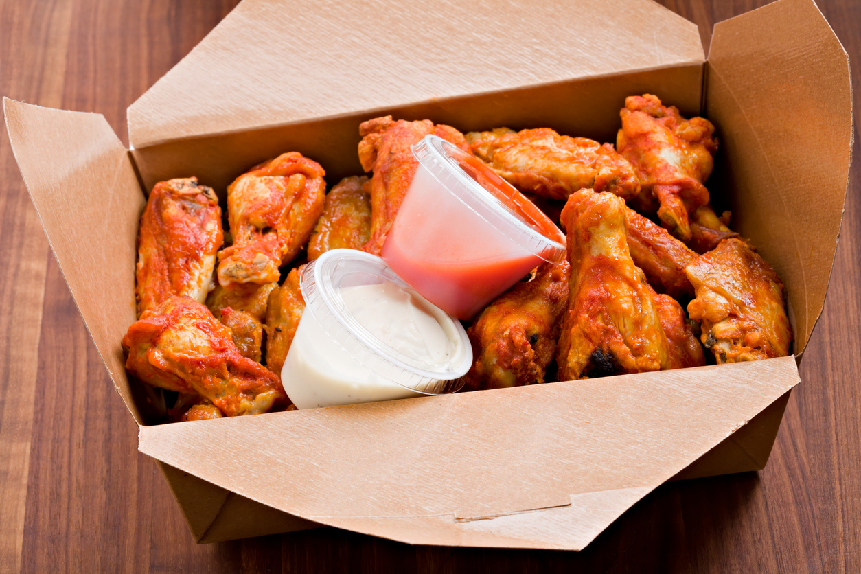 A high angle close up shot of a brown waxed cardboard box filled with hot wings to go | Wings in Manassas
