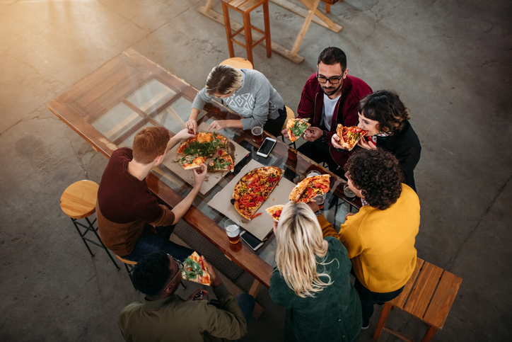 A group of friends eating at a pizza restaurant | Sudley Manor Square